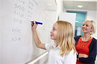 Schoolgirl doing multiplication on white board Stock Photo - Premium Royalty-Freenull, Code: 649-07280099