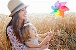 Mother and daughter in wheat field holding windmill