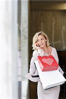 Mid adult woman shopper using mobile phone Stock Photo - Premium Royalty-Freenull, Code: 649-07280427