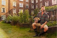 Mid adult man on council estate allotment with bowl of potatoes Stock Photo - Premium Royalty-Freenull, Code: 649-07280488