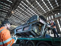 Engineer loading steel part onto truck in factory Stock