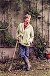 Portrait of mature woman leaning on spade in garden