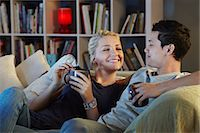 Young couple sitting on sofa with hot drinks Stock Photo - Premium Royalty-Freenull, Code: 649-07280698