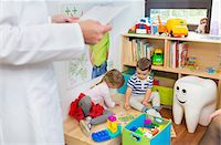 dentistry - Children playing on floor, dentist in foreground Stock Photo - Premium Royalty-Freenull, Code: 649-07280842
