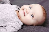 Studio portrait of smiling baby girl lying on back Stock Photo - Premium Royalty-Freenull, Code: 649-07280930