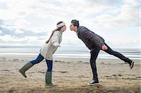 Young couple on one leg, Brean Sands, Somerset, England Stock Photo - Premium Royalty-Freenull, Code: 649-07281037