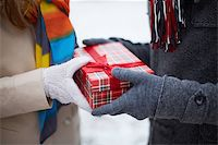 Image of gloved hand of guy giving his girlfriend Christmas present Stock Photo - Royalty-Freenull, Code: 400-07301191