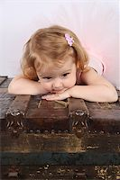 Little ballet girl wearing a pink tutu on an antique trunk Stock Photo - Royalty-Freenull, Code: 400-07302637