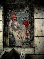 Photo of a hungry zombie covered with blood at the window. Stock Photo - Royalty-Freenull, Code: 400-07306725