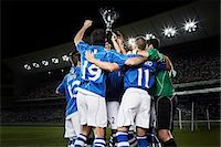 football team - Soccer team cheering with trophy on field Stock Photo - Premium Royalty-Freenull, Code: 6113-07310578