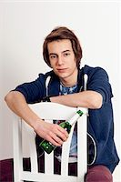 Portrait of teenage boy sitting on chair holding bottle of beer, smiling and looking at camera, studio shot on white background Stock Photo - Premium Royalty-Freenull, Code: 600-07311017