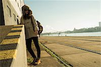 Teenage girl outdoors, wearing trapper hat and sunglasses, standing next to building at loading dock, Mannheim, Germany Stock Photo - Premium Royalty-Freenull, Code: 600-07311093
