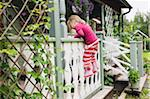 3 year old girl in rubber boots climbing on veranda, Sweden