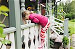 3 year old girl in rubber boots climbs on veranda, Sweden