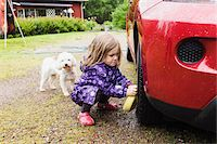 3 year old girl washing a red car while little white dog is watching, Sweden Stock Photo - Premium Royalty-Freenull, Code: 600-07311119