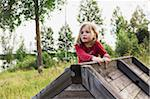 3 year old girl in red shirt climbing on a wooden shed, Sweden