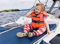 sole - 3 year old girl in orange life jacket sitting on top of motorboat, Sweden Stock Photo - Premium Royalty-Freenull, Code: 600-07311130