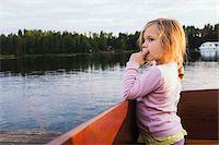 3 year old girl standing in a docked motorboat, looking at the lake, Sweden Stock Photo - Premium Royalty-Freenull, Code: 600-07311132