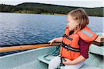 3 year old girl in orange life jacket sitting in a motorboat, fishing, Sweden