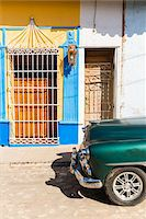 Vintage car on a cobblestone street by colorful wall of house, UNESCO World Heritage Site, Trinidad, Cuba Stock Photo - Premium Royalty-Freenull, Code: 600-07311177