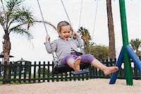 Three year old girl playing in playground on swing, Spain Stock Photo - Premium Rights-Managednull, Code: 700-07311135