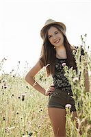 Portrait of teenage girl wearing shorts and straw hat standing in field, smiling and looking at camera, Germany Stock Photo - Premium Royalty-Freenull, Code: 600-07311409