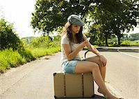 Teenage girl sitting on suitcase on the side of the road, looking at cell phone in summer, Germany Stock Photo - Premium Royalty-Freenull, Code: 600-07311410