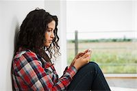 Close-up of teenage girl sitting next to window and using cell phone, Germany Stock Photo - Premium Royalty-Freenull, Code: 600-07311420