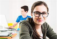 Teenage girl wearing eye glasses and looking at camera, with teenage boy working on project using computer in background, studio shot Stock Photo - Premium Rights-Managednull, Code: 700-07311440