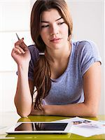 Close-up of young woman with pen and tablet computer, thinking and problem solving, studio shot Stock Photo - Premium Royalty-Freenull, Code: 600-07311599