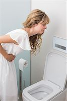 Young woman with stomach sickness about to vomit into a toilet Stock Photo - Royalty-Freenull, Code: 400-07343662