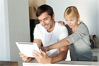 Young Couple Looking At Digital Tablet In Kitchen Stock Photo - Premium Royalty-Freenull, Code: 6106-07349847