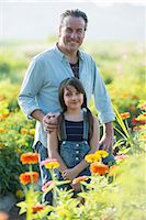 Summer on an organic farm. A man and a girl in a field of flowers. Stock Photo - Premium Royalty-Freenull, Code: 6118-07351115