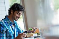 fork - A  man seated checking his phone, and eating in a cafe. Stock Photo - Premium Royalty-Freenull, Code: 6118-07351157