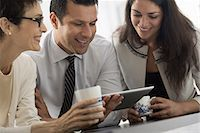 Young professionals at work. Three colleagues, two men and a woman, looking at the screen of a digital tablet. Stock Photo - Premium Royalty-Freenull, Code: 6118-07351363