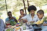 A family picnic in a shady woodland. Adults and children around a table handing around plates and food.