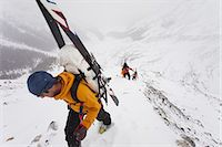 Three skiers ascending a ridge in mist and cloud conditions on the Wapta Traverse, a mountain hut-to-hut ski tour in Alberta, Canada. Stock Photo - Premium Royalty-Freenull, Code: 6118-07351697