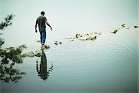 A man walking barefoot across stepping stones away from the shore of a lake. Stock Photo - Premium Royalty-Freenull, Code: 6118-07351874
