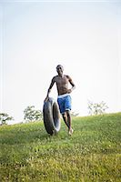 A teenage boy running across the grass rolling a swim float, black tyre in front of him. Stock Photo - Premium Royalty-Freenull, Code: 6118-07351937