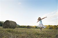 A field full of tall rounded hay bales, and a young girl dancing with her arms outstretched on the stubble field. Stock Photo - Premium Royalty-Freenull, Code: 6118-07352035