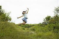A young girl, leaping for joy, kicking up her heels in the air. Stock Photo - Premium Royalty-Freenull, Code: 6118-07352390