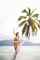 A woman balancing on a leaning palm tree in Las Galeras, Samana Peninsula, Dominican Republic. Stock Photo - Premium Royalty-Freenull, Code: 6118-07352414