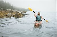 A man paddling a kayak on calm water in misty conditions. New York State, USA Stock Photo - Premium Royalty-Freenull, Code: 6118-07352420