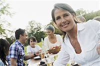 A family and friends having a meal outdoors.  A picnic or buffet in the early evening. Stock Photo - Premium Royalty-Freenull, Code: 6118-07352831