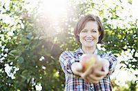 single fruits tree - A woman in a plaid shirt holding a freshly picked apple in her two hands,  in the orchard at an organic fruit farm. Stock Photo - Premium Royalty-Freenull, Code: 6118-07353017