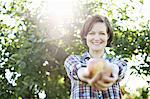 A woman in a plaid shirt holding a freshly picked apple in her two hands,  in the orchard at an organic fruit farm. Stock Photo - Premium Royalty-Freenull, Code: 6118-07353017