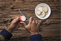 A person holding and slicing sections of a red skinned apple. Stock Photo - Premium Royalty-Freenull, Code: 6118-07353437