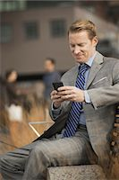 A man sitting on a bench outside a large building,  looking at a cell phone screen or mobile phone. Stock Photo - Premium Royalty-Freenull, Code: 6118-07353622