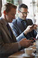 Business people in the city. Two men sitting at a cafe table checking their mobile phone messages and keeping in touch. Stock Photo - Premium Royalty-Freenull, Code: 6118-07353634