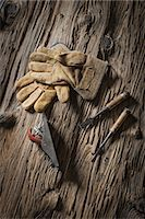 A reclaimed lumber yard workshop. A pair of leather working gloves, and handheld traditional tools. Stock Photo - Premium Royalty-Freenull, Code: 6118-07353641